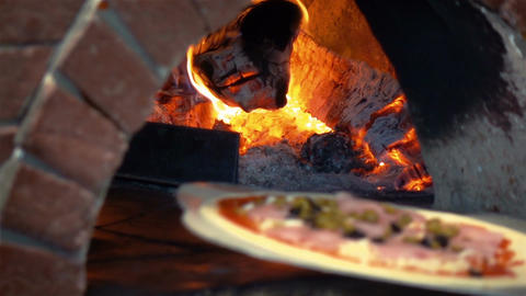 Video of man putting pizza to brick oven in real slow motion Filmmaterial
