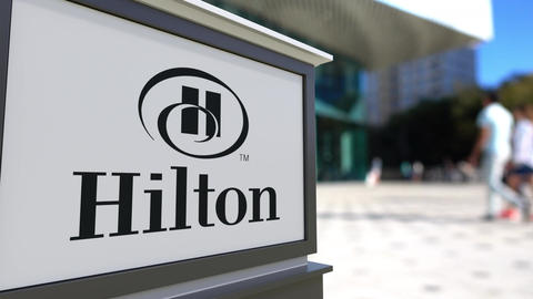 Street signage board with Hilton Hotels Resorts logo. Blurred office center and Footage