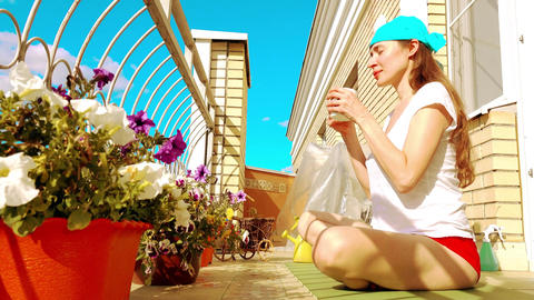Young beutiful woman drinking tea or coffee on the sunny terrace Footage