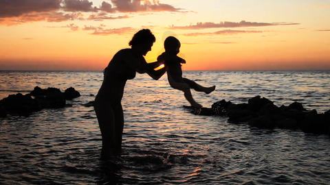 Mother of the child bathed in the sea at sunset Footage
