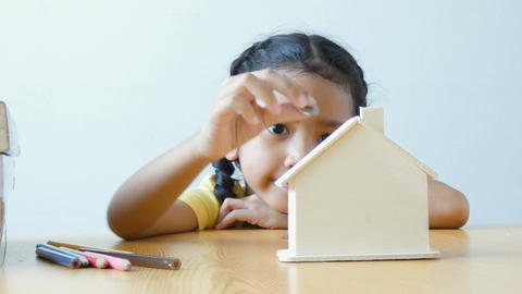 Asian little girl putting money coin into clear house bank metaphor saving money Live Action