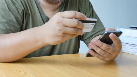 Close up shot hands of man using smart phone and holding credit card metaphor Footage