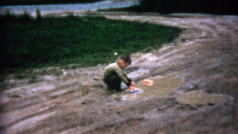 1962: Boy playing with toy boats in sad muddy driveway puddle Footage