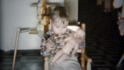 1962: Toddler boy feeding and kissing plastic baby doll Footage