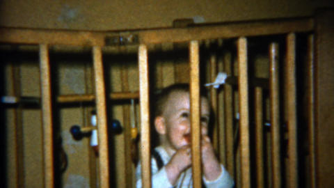 1962: Baby behind jail crib bars chews on shoelaces Footage