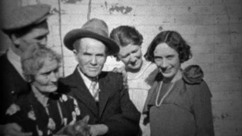 1933: Extended family petting family car outside of depression era home Footage