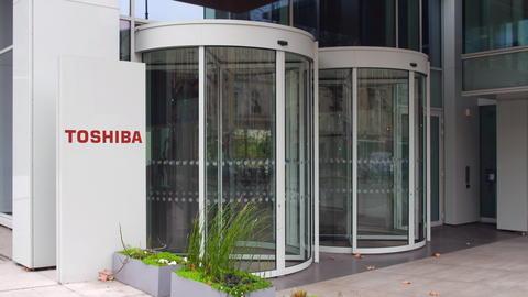 Street signage board with Toshiba Corporation logo. Modern office building Fotografía