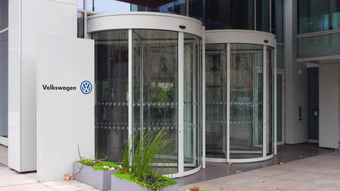 Street signage board with Volkswagen logo. Modern office building. Editorial 4K Live Action