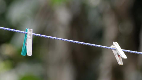 Mid close bokeh shot of two hanging cloth clips on a rope 画像