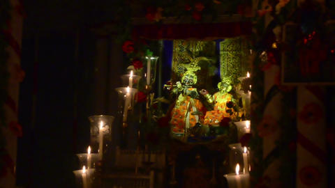 Mid shot of a statue of Lord Krishna and Radha surrounded by beautiful candles Archivo