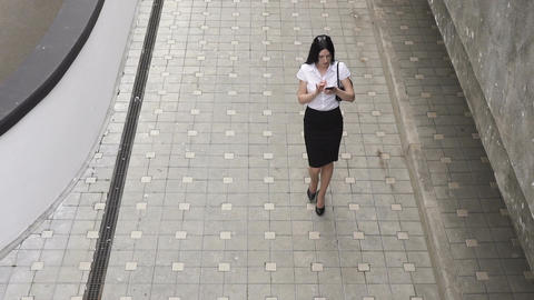 Business woman walking and using a smart phone Footage