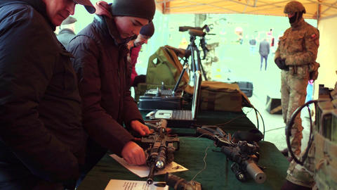 KRAKOW, POLAND - JANUARY, 14, 2017 People examine weapons and army equipment at Footage