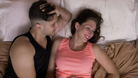 Young relaxed couple cuddling and sitting in bed him tickling her joking and Footage
