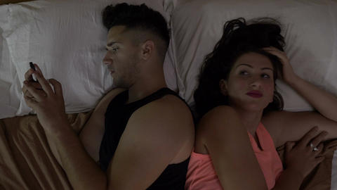 Couple in bed at night husband addicted to smartphone on internet social media Live Action