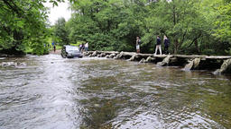 Land Rover driving through a ford at River Barle Tarr Steps clapper bridge Filmmaterial