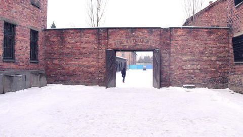 Steadicam shot of concentration camp brick building in falling snow. 4K clip Footage