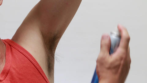 close up shot of man spraying deodorant under his arm Footage
