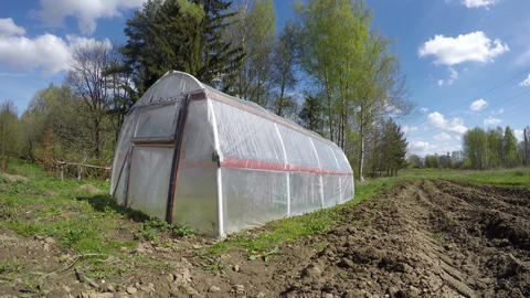 greenhouse in spring wind and clouds motion in farm. Time lapse Footage
