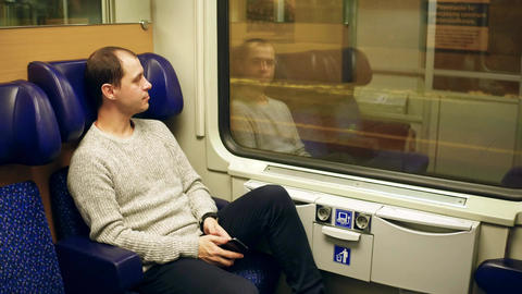 Man in sweater taking his seat in a train and using his mobile phone Footage