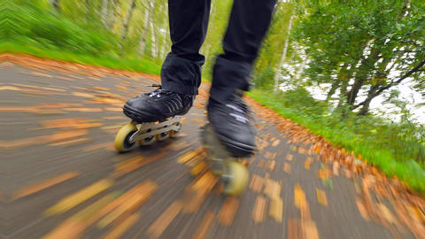 Outdoor inline skating on wet slippery asphalt in autumnal forest. Man legs in Footage