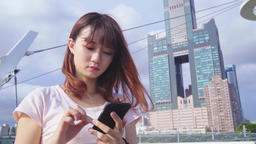 young Asian woman using smartphone Archivo