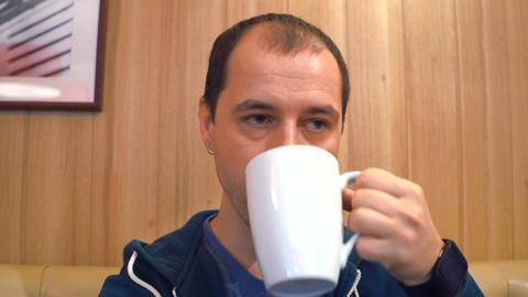 Sleepy man having big cup of coffee to keep him awake in a cafe Footage