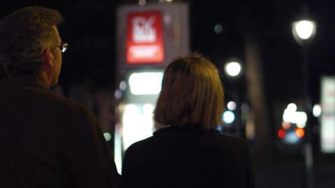 Mature couple walking on the city street at night ビデオ
