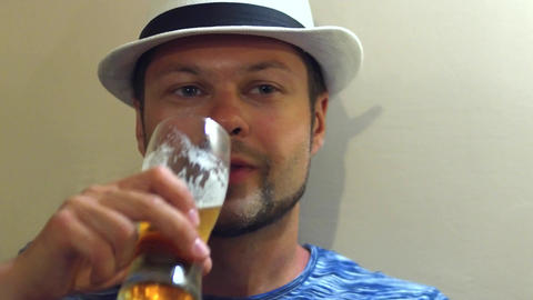 Young handsome bearded man wearing hat drinking beer Live Action