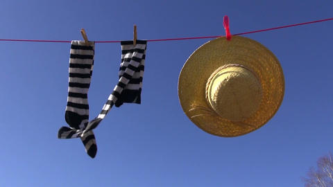 laundry line with woman socks and straw hat in wind on sky background Footage