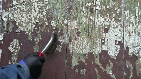 scrape old paint from wooden house wall with metal brush Footage