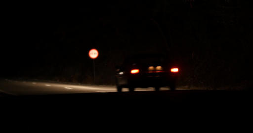 Car that goes by speed on a paved road all night illuminating the road with its Live Action