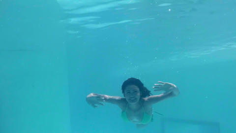 Pretty woman swimming underwater in pool Footage