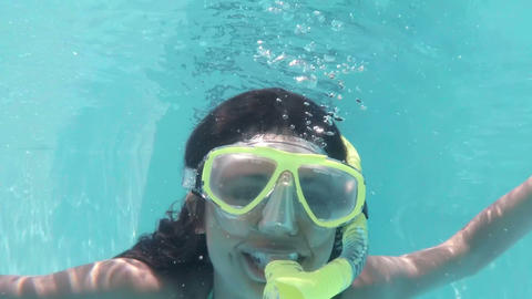 Pretty brunette diving into swimming pool wearing snorkel Footage