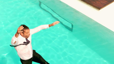 Businessman with briefcase jumping in the swimming pool Live Action