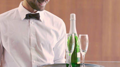 Smiling waiter holding champagne bottle and flute Footage