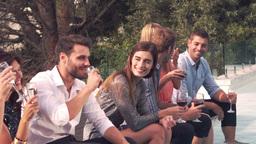 Happy friends having a drink poolside ビデオ