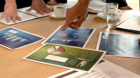 Graphics on table looked by business people in meeting Footage