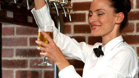 Barmaid pulling a glass of beer Live Action
