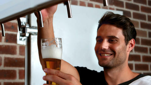 Smiling barman pulling a pint of beer Live Action