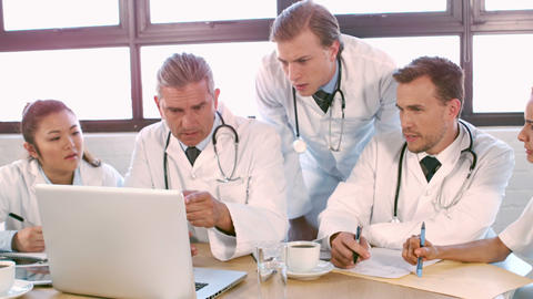 Medical team talking together while looking laptop Live Action