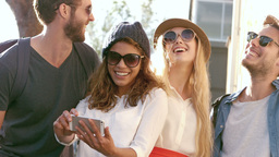 Smiling hipster friends looking at smartphone Footage