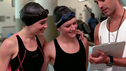 Fit swimmers discussing with trainer Footage