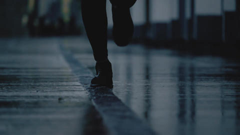 Super slow motion close-up shot of female runner's feet running on wet pavement Footage