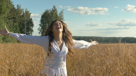 Beautiful young girl is happy on a wheat field Footage
