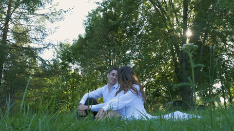 A beautiful couple in white clothes is sitting on the green grass. Romantic date Footage