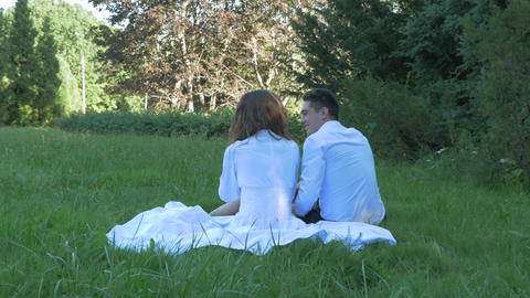 Romantic couple in white clothes embrace and kiss on date. They are sitting on Footage