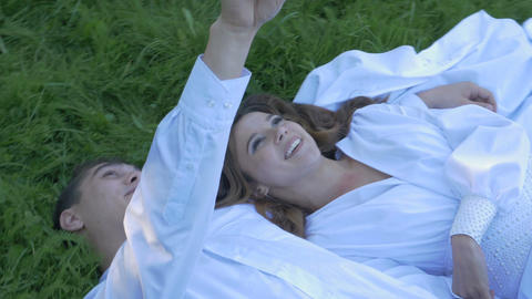 Beautiful girl and her boyfriend lie on the grass and look at the sky. Happy Footage