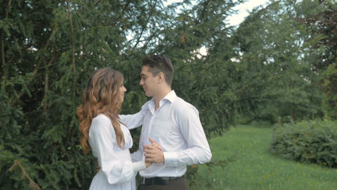A beautiful couple in white suits hugs on a date Footage