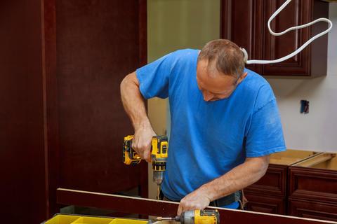 technician man installing kitchen cabinets Foto