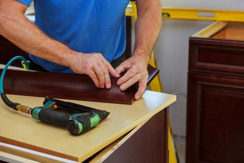 Carpenter brad using nail gun to Crown Moulding on kitchen cabinets framing trim Foto